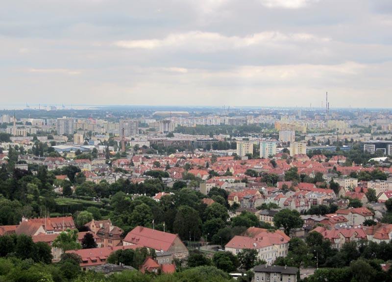 Widok z Pachołka 100,8 m n.p.m - czerwone dachy starej zabudowy dzielnicy Oliwa, w oddali Baltic Arena i morze